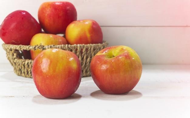 Gros plan deux pommes avec des gouttes d'eau mis sur planche de bois, lumière floue autour
