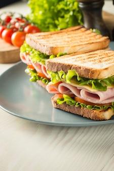 Gros plan de deux sandwichs au bacon, salami, prosciutto et légumes frais sur une planche à découper en bois rustique. concept de sandwich au club.
