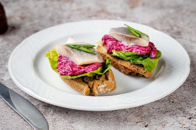 Gros plan de deux sandwichs au hareng maison avec de la betterave et des feuilles vertes sur plaque blanche