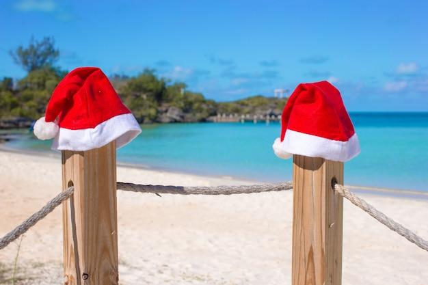 Gros plan, deux, santa, chapeaux, sur, barrière, à, plage blanche tropicale