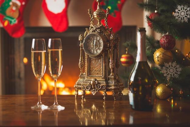 Gros plan de deux verres de champagne sur la table à côté de la vieille horloge montrant minuit au salon décoré pour noël