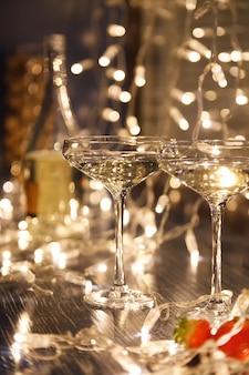 Gros plan de deux verres de vin blanc dans des verres en cristal transparent, des fraises et des guirlandes légères