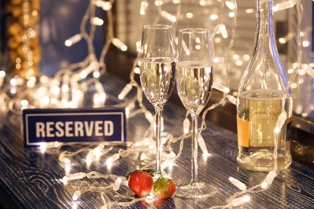 Gros plan de deux verres de vin blanc dans des verres en cristal transparent, des fraises, des signes réservés et des guirlandes lumineuses