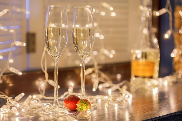 Gros plan de deux verres de vin blanc dans des verres en cristal transparent et des guirlandes lumineuses