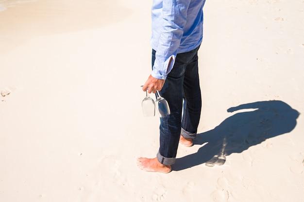 Gros plan de deux verres à vin dans la main d'un homme sur la plage de sable blanc