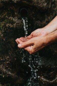 Un gros plan de deux vieilles mains prenant de l'eau pour boire à partir d'une police naturelle dans la forêt