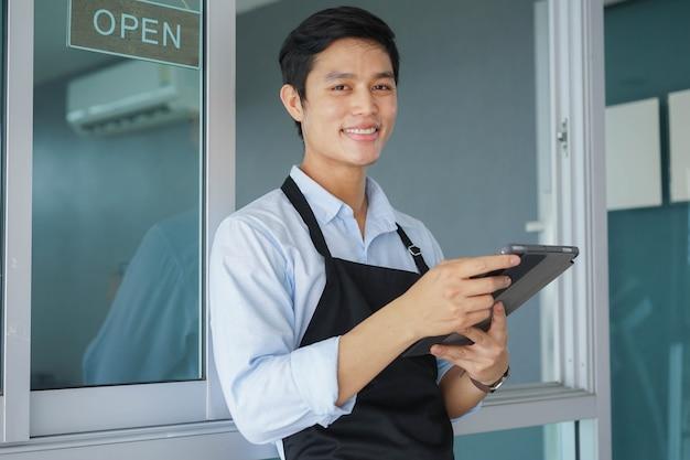 Gros plan devant un jeune homme propriétaire d'entreprise tenant une tablette et s'appuyant sur un magasin avec un panneau d'affichage ouvert pour promouvoir et informer la réouverture du café après la pandémie de coronavirus pour le concept d'entreprise et de démarrage