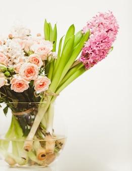 Gros plan de différentes fleurs debout dans un vase en verre