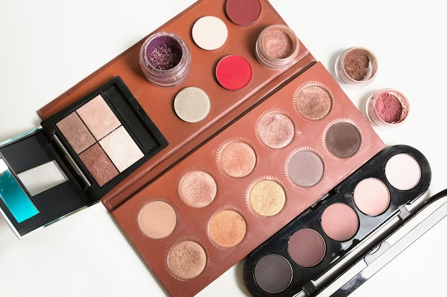 Gros plan sur différentes palettes de maquillage avec des pigments pour les yeux et des paillettes sur fond blanc