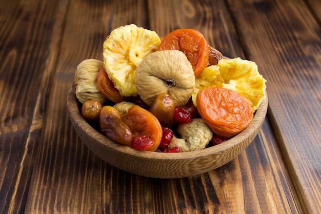 Gros plan sur différents fruits secs dans l'arc brun sur la surface en bois