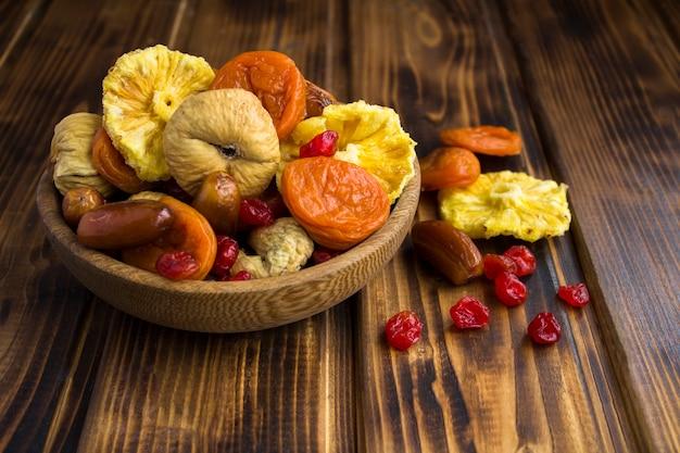 Gros plan sur différents fruits secs dans l'arc brun sur la table en bois
