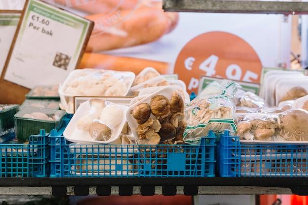 Gros plan de différents types de champignons emballés dans la caisse bleue