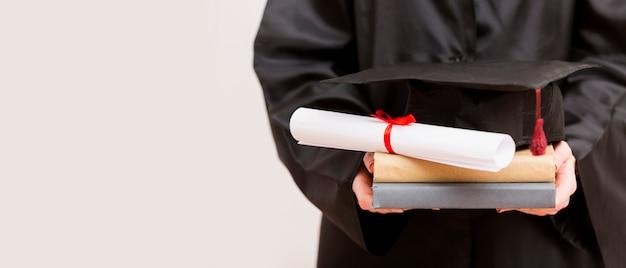 Gros plan, diplômé, tenue, livres