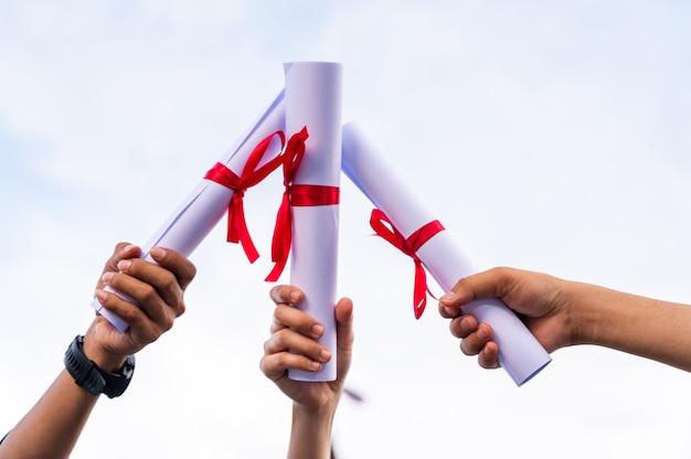 Gros plan des diplômés titulaires de diplômes en main