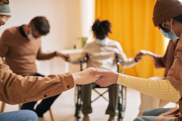Gros plan sur divers groupes de personnes se tenant la main dans un cercle de soutien pendant la séance de thérapie, toutes portant des masques, espace de copie