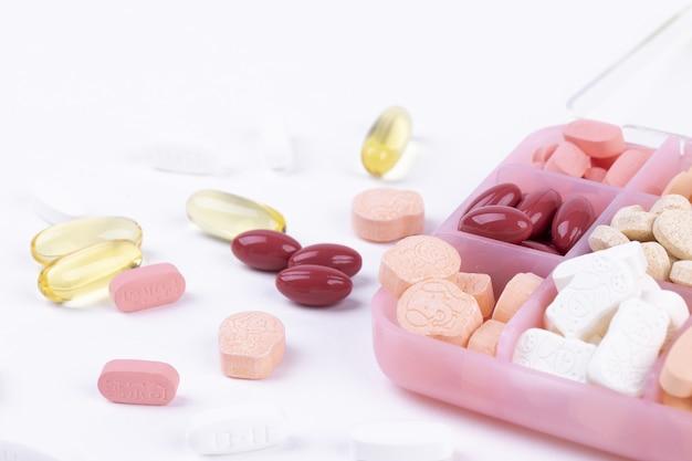 Gros plan de divers produits pharmaceutiques dans un récipient pour médicaments sur fond blanc