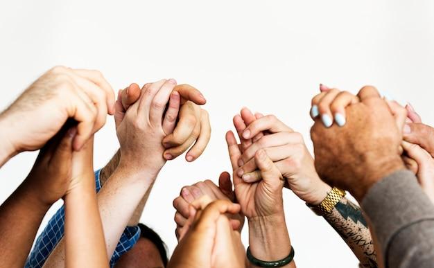 Gros plan de diverses personnes se tenant la main