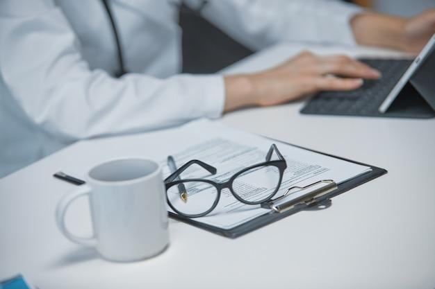 Gros plan sur un document signé par un médecin allongé sur la table à côté de lunettes et d'un stylo