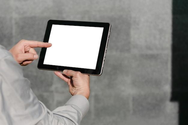 Gros plan, doigt devant une maquette d'écran de tablette, entre les mains d'un homme d'affaires. dans le contexte d'un mur de béton gris.