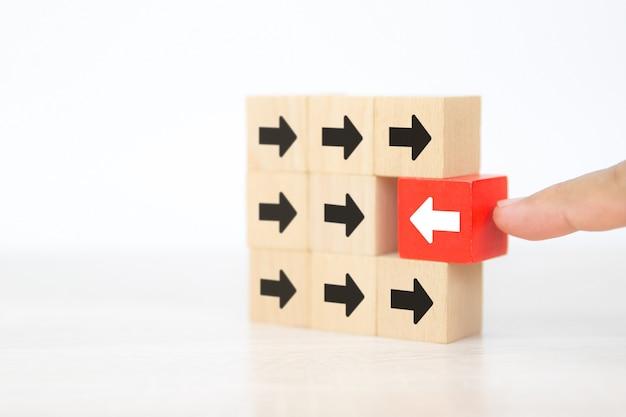 Gros plan doigt pousser bloc en bois rouge avec l'icône de la flèche.
