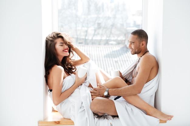Gros plan doux jeunes amants souriant à la caméra assis près de la fenêtre en verre à l'intérieur