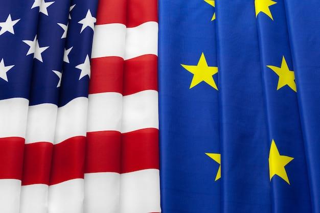 Gros plan de drapeaux des états-unis et de l'union européenne, couchés ensemble sur la table
