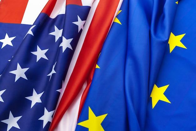 Gros plan de drapeaux des états-unis et de l'union européenne se trouvant ensemble sur la table