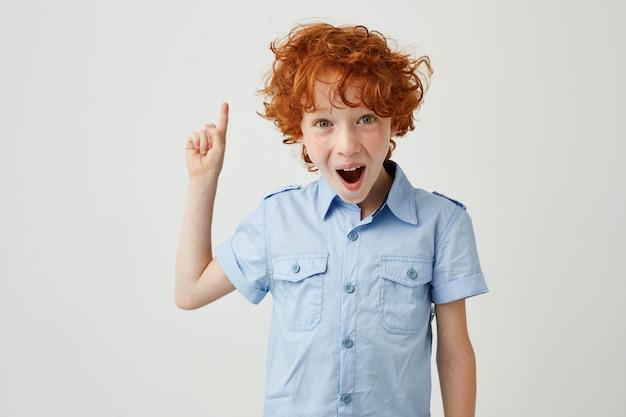 Gros plan de drôle de garçon au gingembre avec des taches de rousseur pointant vers le haut avec la bouche ouverte et l'expression du visage idiot.