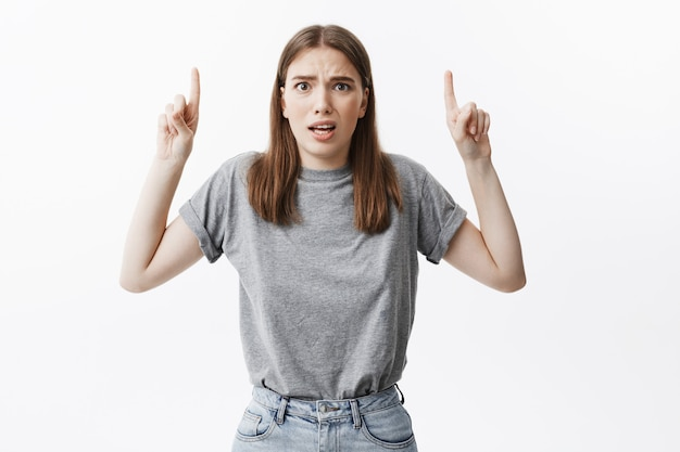 Gros plan de drôle jeune fille séduisante étudiante aux cheveux noirs dans des vêtements décontractés avec un air confus, pointant à l'envers avec des index sur les deux mains. copiez l'espace.