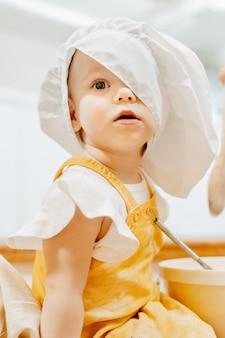 Gros plan d'un drôle de petit enfant caucasien dans un grand chapeau de cuisinier regarde avec surprise l'appareil photo