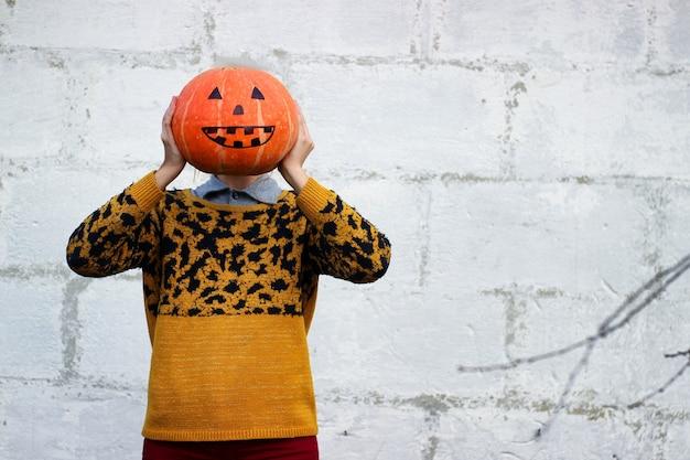Gros plan drôle de tête de citrouille orange que la fille tient dans ses mains au lieu de sa tête.
