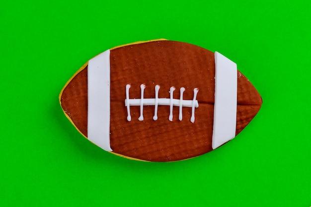 Gros plan du ballon de football américain isolé sur fond vert. vue de dessus.