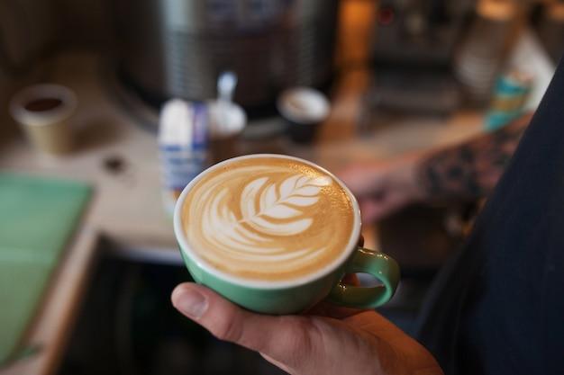 Gros plan du barista tenant un cappuccino aromatique. café prêt à vendre. mains mâles tenant une tasse de café.