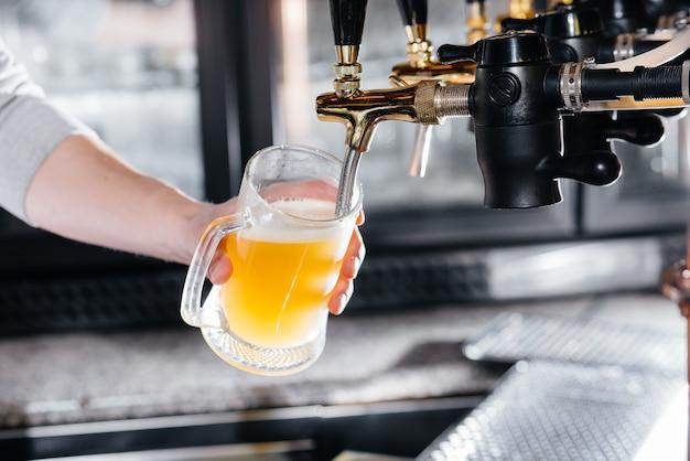 Gros plan du barman remplissant une chope de bière légère