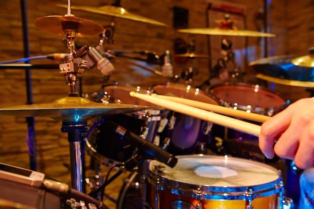 Gros plan du batteur jouant du kit de batterie en studio