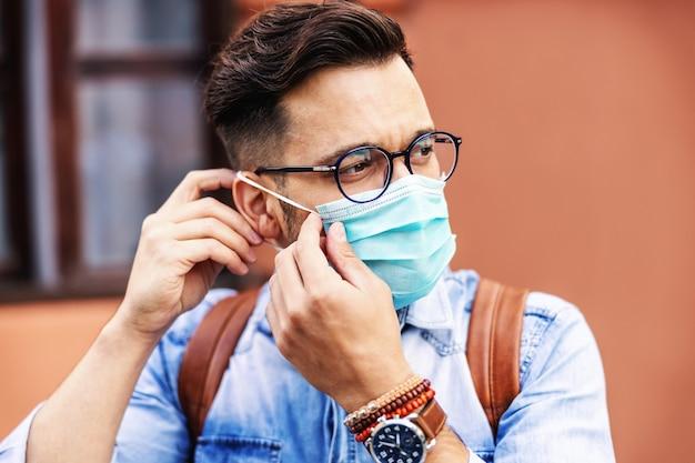 Gros plan du beau hipster mettant un masque sur son visage pendant l'épidémie de virus corona.