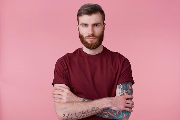 Gros plan du beau jeune homme avec barbe au gingembre et main tatouée, bras croisés et regardant à huis clos sans émotion isolée sur fond rose.