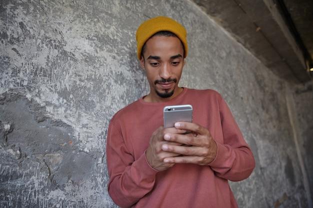 Gros plan du beau jeune homme barbu à la peau foncée tenant le téléphone portable dans les mains levées et à la recherche à l'écran avec le visage concentré, posant sur le mur de béton dans des vêtements décontractés
