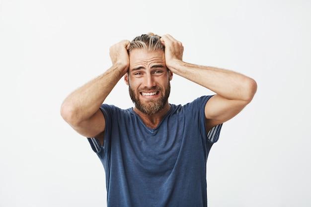 Gros plan du beau mec malheureux avec barbe tenant les cheveux avec les mains