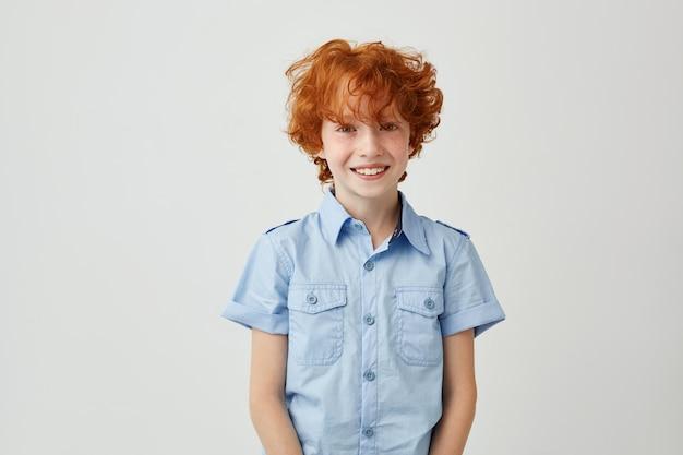 Gros plan du beau petit garçon au gingembre avec les cheveux ébouriffés et les taches de rousseur