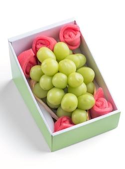 Gros plan du beau raisin vert muscat sanctuaire en boîte isolé sur blanc
