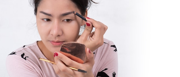 Gros plan du beau visage de jeune femme asiatique se maquiller. l'artiste applique un fard à paupières sur son sourcil avec un pinceau et un crayon. dame a fermé les yeux avec relaxation