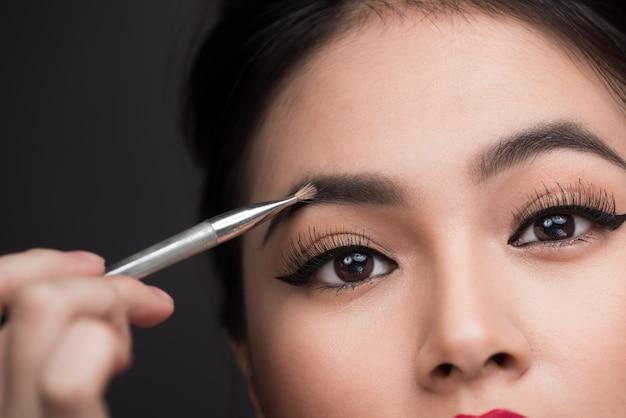 Gros plan du beau visage de la jeune femme asiatique se maquiller. l'artiste applique un fard à paupières sur son sourcil avec un pinceau