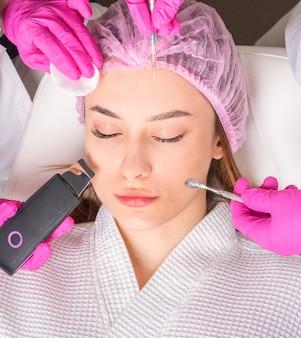 Gros plan du beau visage d'une jeune femme. beaucoup de mains tenant des outils de cosmétologie près du visage d'un patient