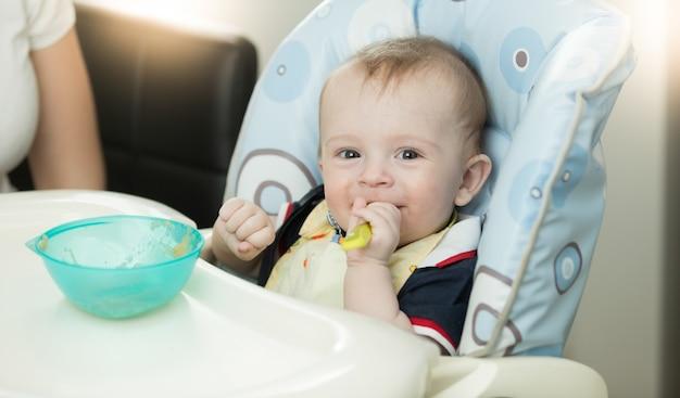 Gros plan du bébé assis dans une chaise haute et tenant une cuillère