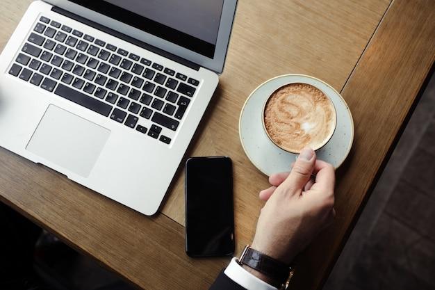 Gros plan du bel homme d'affaires, travaillant sur un ordinateur portable argenté au restaurant