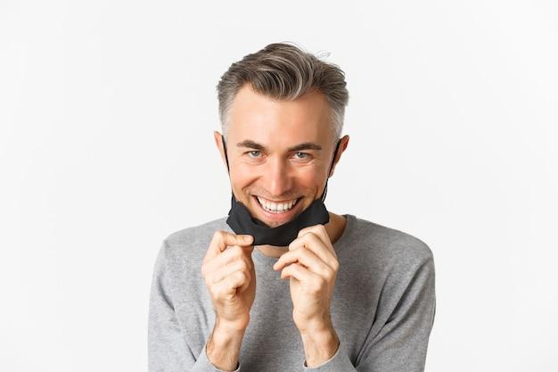 Gros plan du bel homme d'âge moyen, décoller le masque médical et à la recherche de plaisir