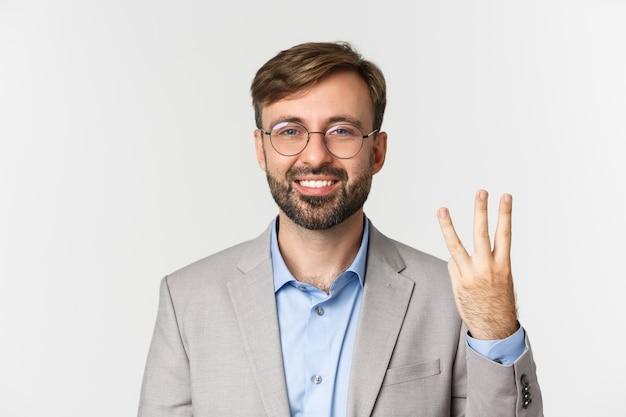 Gros plan du bel homme barbu à lunettes et costume gris, montrant le numéro trois