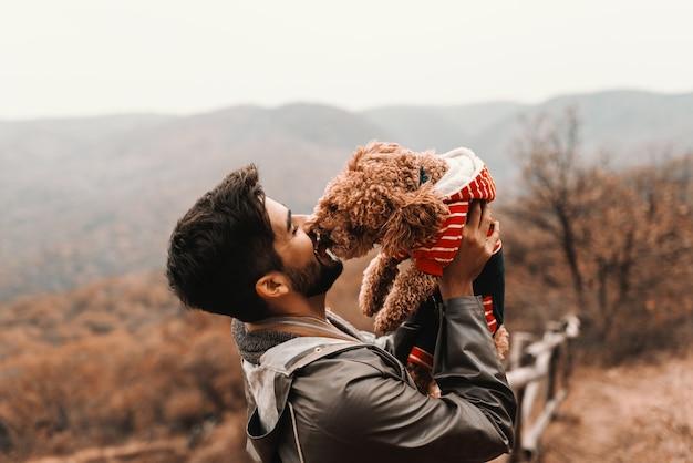Gros plan du bel homme tenant son caniche abricot tandis que le caniche le léchant