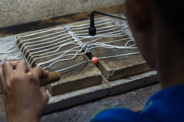 Gros plan du bijoutier artisanal collier en argent avec flamme.
